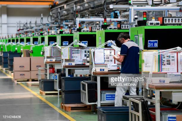 An employee works during his shift at the production line of the Codogno-based Italian multinational company MTA, specialized in electromechanical...