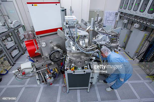 An employee works in a clean room during the etching process of semiconductor wafer production inside the new Robert Bosch GmbH research and...