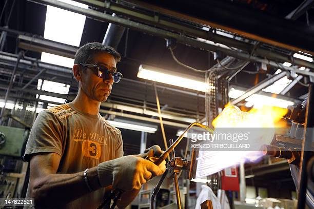 An employee works in a glass etching company on June 29 2012 in JoinvillelePont near Paris AFP PHOTO / KENZO TRIBOUILLARD