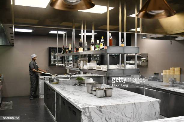 An employee works in a restaurant kitchen at the Roseate New Delhi hotel operated by the Bird Group in New Delhi India on Saturday Aug 19 2017 The...
