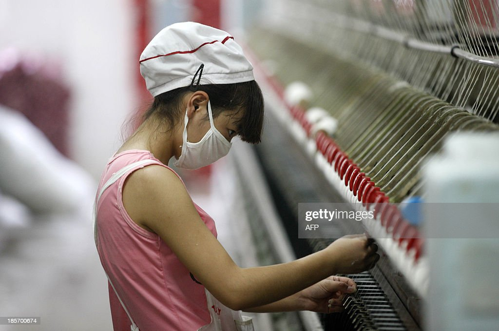 An employee works in a textile factory in Huaibei, east China's Anhui province on October 24, 2013. China's manufacturing activity expanded at its strongest pace in seven months in October, British banking giant HSBC said on October 24, adding to evidence the world's second-largest economy is recovering. CHINA