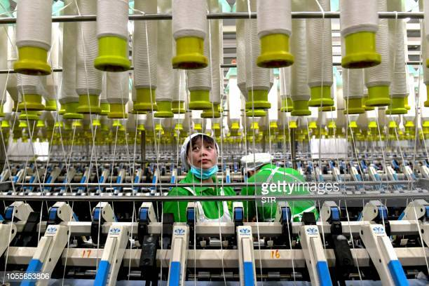 An employee works in a textile factory in Xiayi county in Shangqiu in China's central Henan province Chinese factory activity slowed in October...
