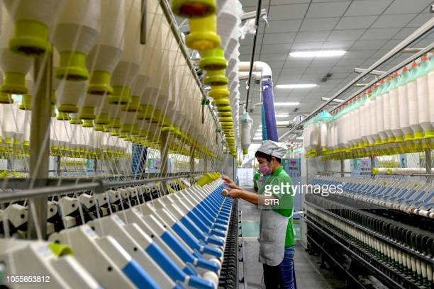 An employee works in a textile factory in Xiayi county in Shangqiu in China's central Henan province. - Chinese factory activity slowed in October,...