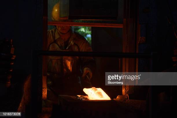 An employee works in front of a furnace as he makes vehicle parts at an Asahi Tekko Co factory in Nishio Aichi Prefecture Japan on Wednesday Aug 1...