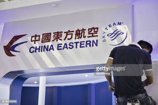 An employee works in front of China Eastern Airlines Corp signage on display at the China International Aviation Aerospace Exhibition in Zhuhai China...