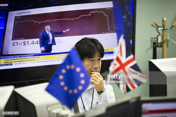 An employee works in front of computer monitors near a European Union flag left and a British Union Flag also known as a Union Jack at a foreign...