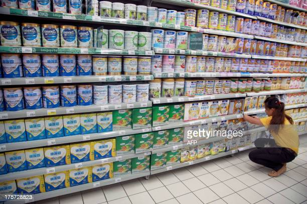 An employee works in front of shelves of baby milk in a supermarket in Haikou in southern China's Hainan province on August 7 2013 China has fined...