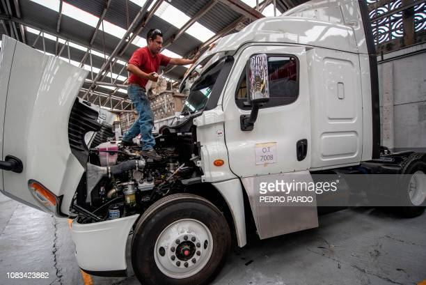 An employee works in the armouring of a semi trailer truck at a plant in Ecatepec Mexico state on October 23 2018 In a technological race with...