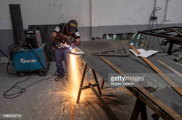 An employee works in the armouring of semi trailer trucks at a plant in Ecatepec Mexico state on October 23 2018 In a technological race with...