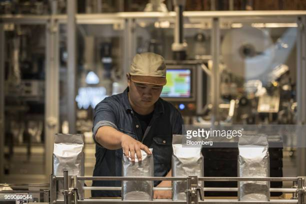 An employee works in the coffee beanpackaging area inside the Starbucks Corp Reserve Roastery store in Shanghai China on Friday May 11 2018...