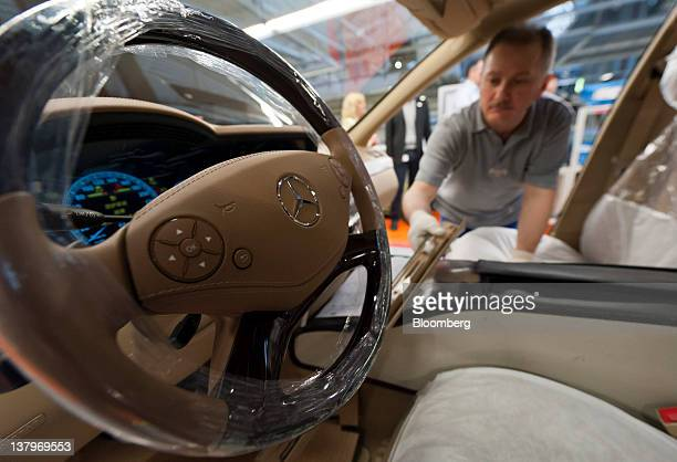 An employee works inside a Daimler AG MercedesBenz Sclass automobile as it travels along the production line inside the company's factory in...