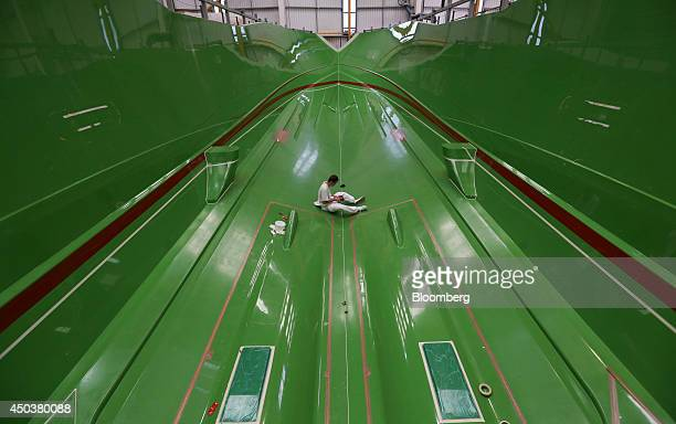An employee works inside the hull of 28 meter Sunseeker yacht produced by Sunseeker International Ltd a unit of China's Dalian Wanda Group during...