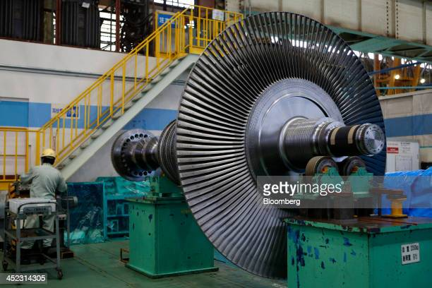 An employee works near a steam turbine rotor assembled at Hitachi Ltd's Kaigan factory of Hitachi Works in Hitachi Ibaraki Prefecture Japan on...