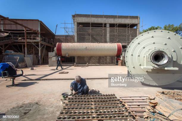 An employee works near two new ball mills in a construction site for new facilities at the Shabbir Tiles Ceramics Ltd production facility in Karachi...
