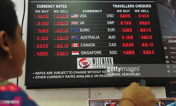 An employee works next to a board showing the exchange rate of Indian rupees to other currencies at a foreign exchange dealer in Mumbai on August 6...