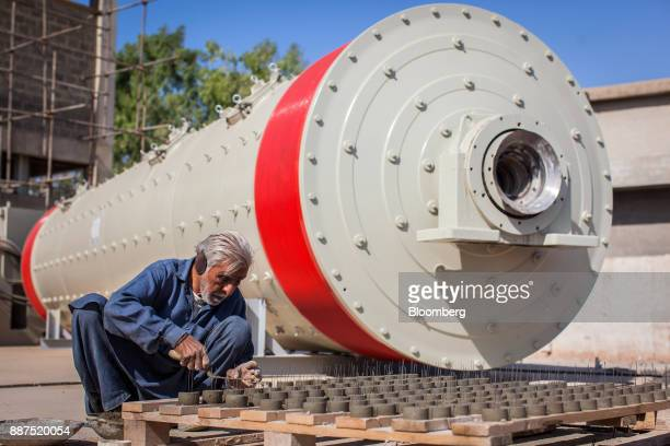 An employee works next to a new ball mill in a construction site for new facilities at the Shabbir Tiles Ceramics Ltd production facility in Karachi...