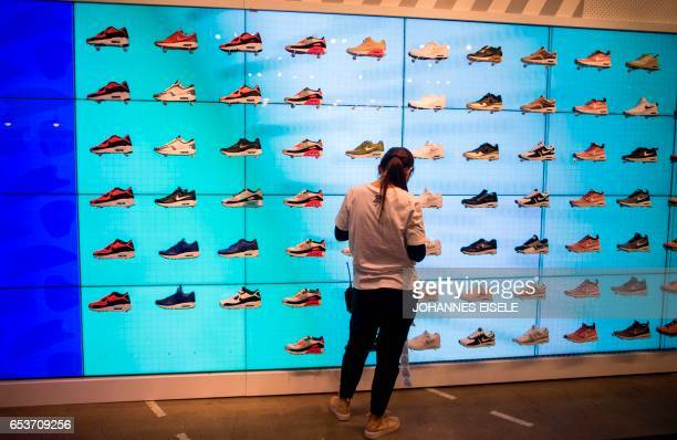 An employee works next to shoes on display inside the flagship store of sportinggoods giant Nike in Shanghai on March 16 2017 US sportinggoods giant...