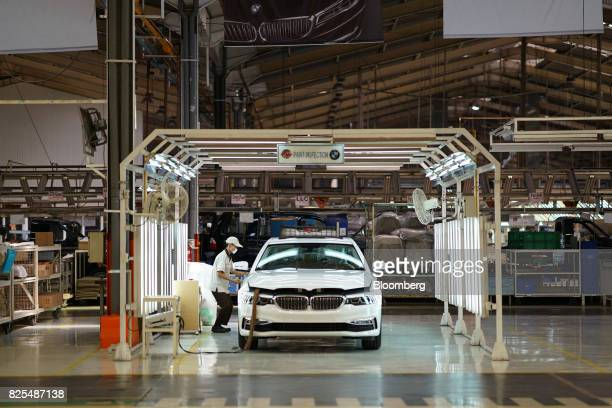 An employee works on a BMW 530i sedan in the paint inspection area on the production line at a PT Gaya Motor plant in Jakarta Indonesia on Wednesday...