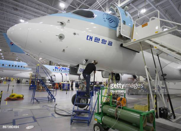An employee works on a Bombardier Inc CS300 airplane with a livery for Korean Air Lines Co at the Bombardier hangar in Mirabel Quebec Canada on...