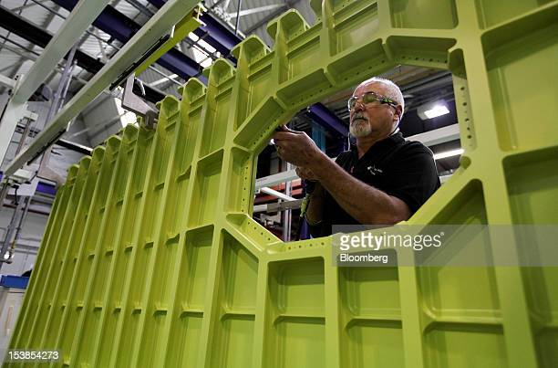 An employee works on a component for an Airbus SAS aircraft a unit of European Aeronautic Defence Space Co at GKN Plc's Aerospace factory in Filton...