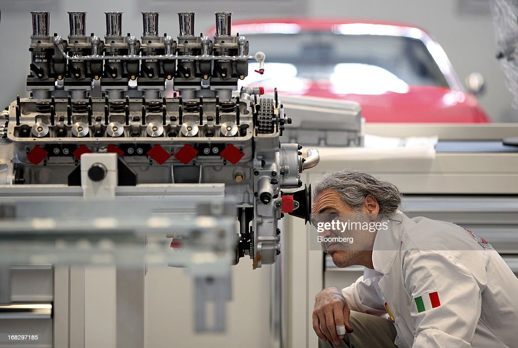 An employee works on a Ferrari 250 LM engine in the vintage cars workshop at Ferrari SpA's automobile plant in Maranello, Italy, on Wednesday, May 8, 2013. Ferrari SpA, the Italian supercar manufacturer owned by Fiat SpA, plans to reduce sales to fewer than 7,000 vehicles this year to 'maintain the exclusivity' of the brand. Photographer: Alessia Pierdomenico/Bloomberg via Getty Images