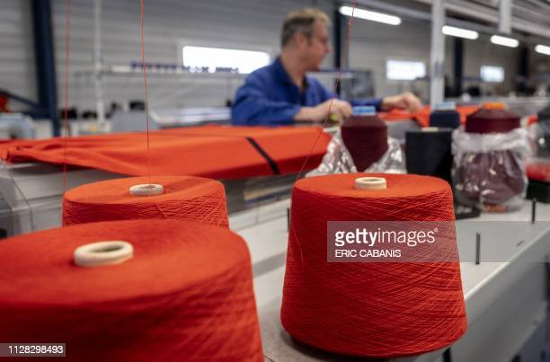 an employee works on a knitting machine at a factory specialised in picture