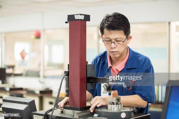 An employee works on a machine in the molding room at the HiP International Ltd production facility in Singapore on Thursday Oct 5 2017 HiP is...