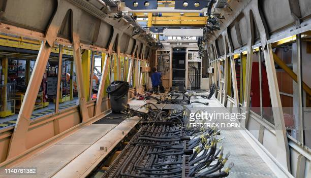 An employee works on a motor coach of a TGV dupleix rail car highspeed train at the SNCF Technicentre assembling plant in Bischheim eastern France on...