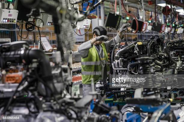 An employee works on a motor for a Nissan Micra automobile on the engine assembly line inside the Renault SA factory in Flins France on Thursday Feb...
