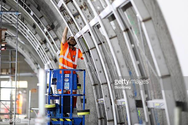 An employee works on a section of the platform wall at the Tottenham Court Road Crossrail station in London, U.K., on Wednesday, Nov. 16, 2016. The...