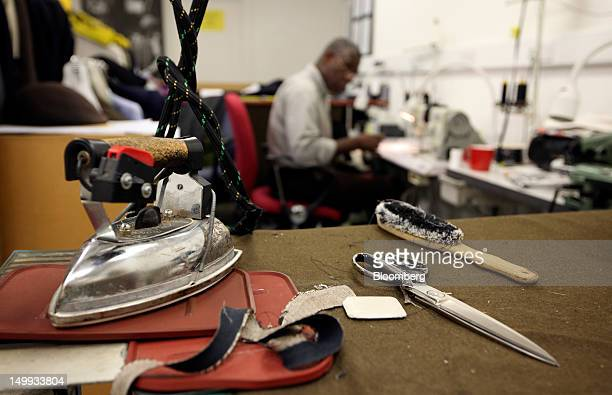 An employee works on a sewing machine in the workshop at the Gieves Hawkes store owned by Trinity Ltd on Saville Row in London UK on Tuesday Aug 7...