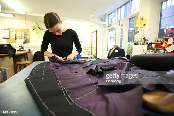 An employee works on a suit in the workshop at the Gieves Hawkes store owned by Trinity Ltd on Saville Row in London UK on Tuesday Aug 7 2012 UK...