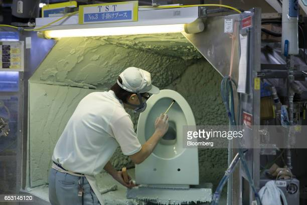An employee works on a toilet bowl in the painting section of the Toto Ltd factory in Kitakyushu Fukuoka Japan on Wednesday Jan 25 2017 After...