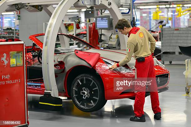 An employee works on a tourism car held on a pincer in the Ferrari factory on December 5 2012 in Maranello The Ferrari 45 buildings's factory where...
