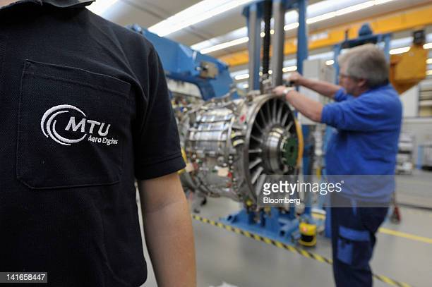 An employee works on a TP400D6 engine manufactured by MTU Aero Engines Holding AG for use on an Airbus SAS A400M military transporter aircraft in...