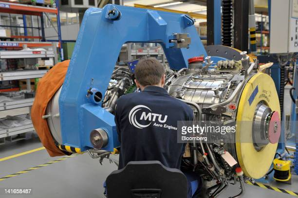 An employee works on a TP400D6 engine manufactured by MTU Aero Engines Holding AG for use on an Airbus SAS A400M military transporter aircraft at the...