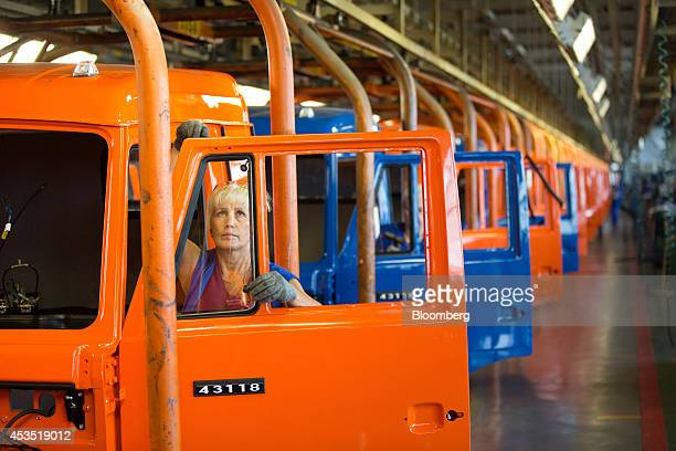 An employee works on a truck cabin door assembly as it moves along the production line at the OAO KamAZ plant in Naberezhnye Chelny Russia on Monday...