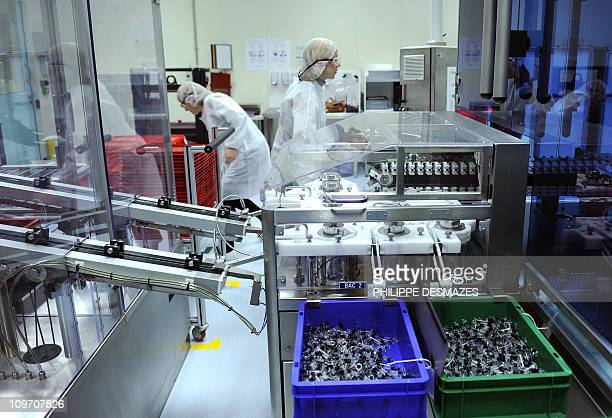 An Employee works on a vaccine assembly line on February 1 2011 in the vaccine production factory of SanofiPasteur the vaccine branch of French...