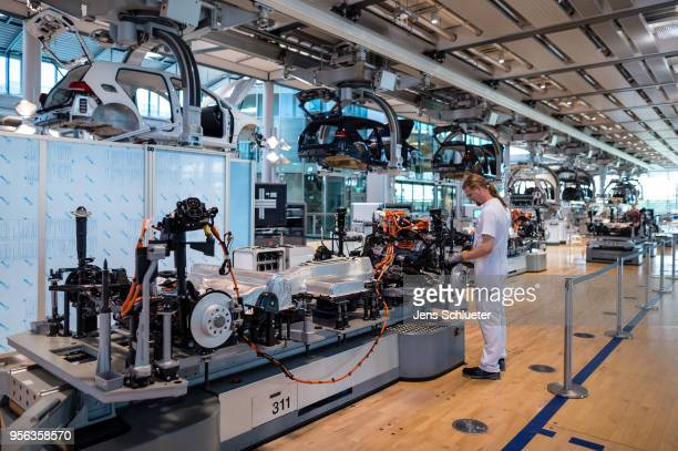 An employee works on a Volkswagen eGolf electric automobile on the assembly line inside the Volkswagen AG factory on May 8 2018 in Dresden Germany...