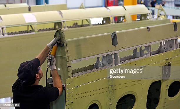An employee works on a wingbox section of an Airbus SAS aircraft a unit of European Aeronautic Defence Space Co at GKN Plc's Aerospace factory in...
