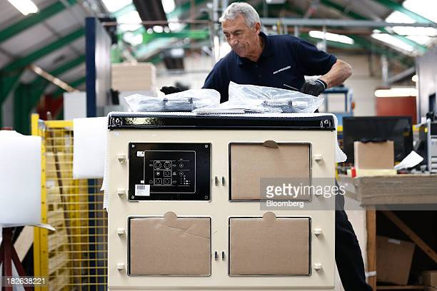 An employee works on an AGA 3oven Total Control range cooker produced by AGA Rangemaster Plc during the manufacturing process at the company's plant...