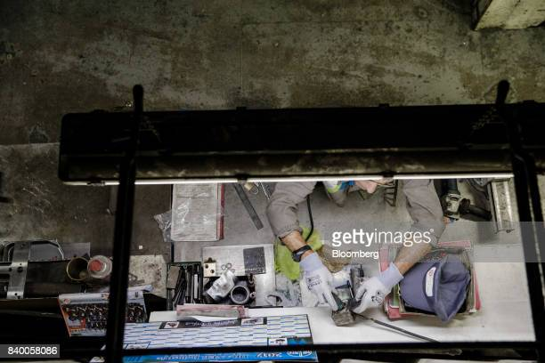 An employee works on an automobile part in the GMS auto components factory in La Souterraine La Creuse region France on Monday July 24 2017 Even as...