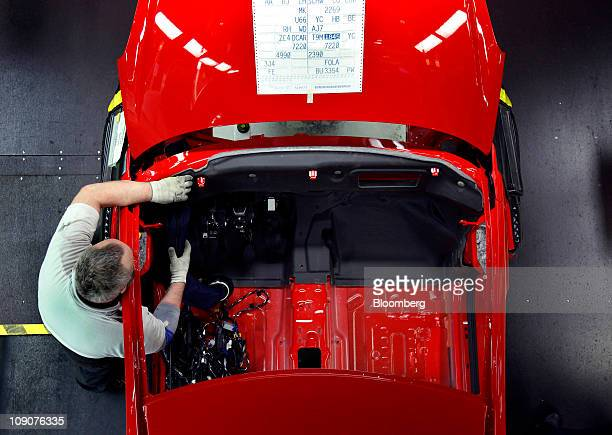 An employee works on an Opel Corsa automobile as it passes along the production line at the General Motor Co's Adam Opel plant in Eisenach Germany on...