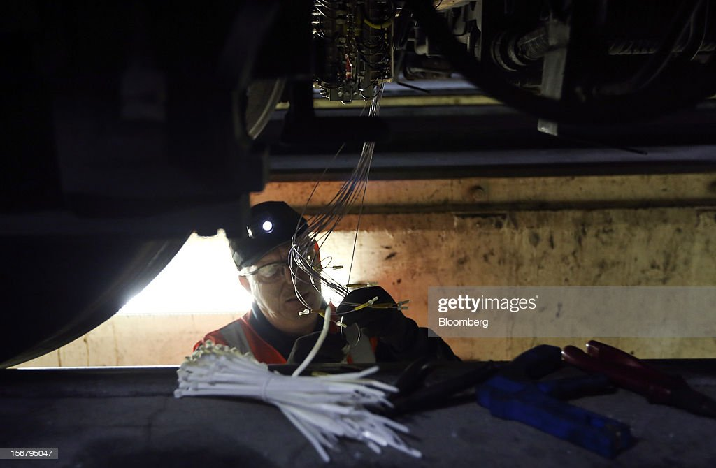 An employee works on electrical wiring beneath a London Underground Northern Line train at Alstom SA's Traincare Centre in the Golders Green district of London, U.K., on Wednesday, Nov. 21, 2012. Transport for London (TFL), who oversee the U.K. capital's public transport system, issued 300 million pounds ($476 million) of bonds five months ahead of schedule to take advantage of investor demand as it continues its 35 billion-pound transport investment program. Photographer: Chris Ratcliffe/Bloomberg via Getty Images