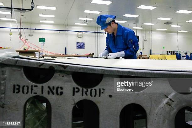 An employee works on producing parts for Boeing Co airplanes at the Boeing Composites Tianjin Co Ltd plant in Tianjin China on Wednesday June 13 2012...