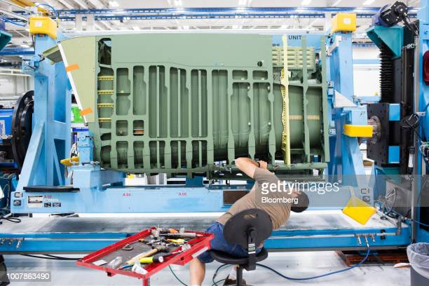 An employee works on the aft fuselage of a Boeing Co F15 Strike Eagle fighter aircraft at the Boeing Defense Space Security facility in St Louis...