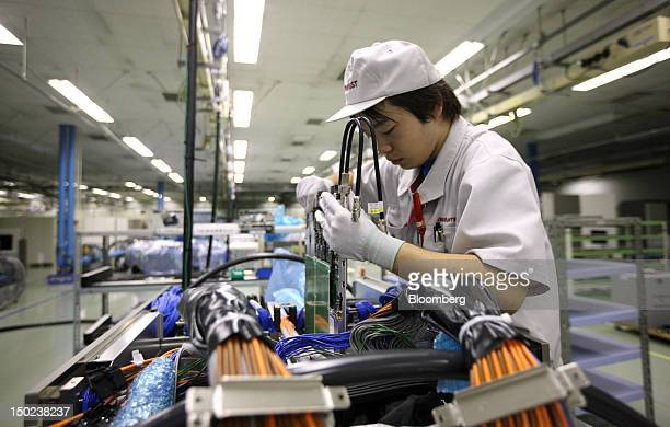 An employee works on the assembly line for semiconductor testers at the Advantest Corp plant in Ora Town Gunma Prefecture Japan on Friday Aug 10 2012...