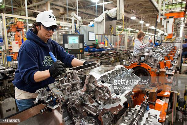 An employee works on the assembly line installing parts on the Duratech 35 V6 engine at the Ford Motor Co Engine Plant in Lima Ohio US on Friday...
