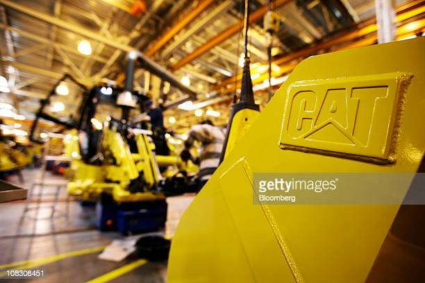 An employee works on the assembly of a Caterpillar Inc 'backhoe' digger on the production line at the factory in Desford UK on Tuesday Jan 25 2011...
