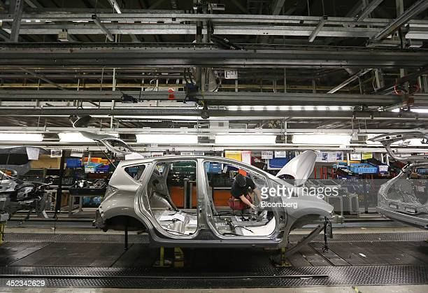 An employee works on the chassis of a new Nissan Note automobile manufactured by Nissan Motor Co on the production line at the company's plant in...
